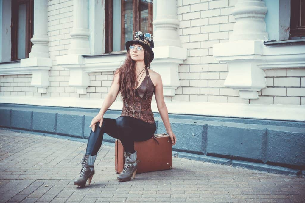 Woman wearing faux leather leggings while sitting on her suitcase