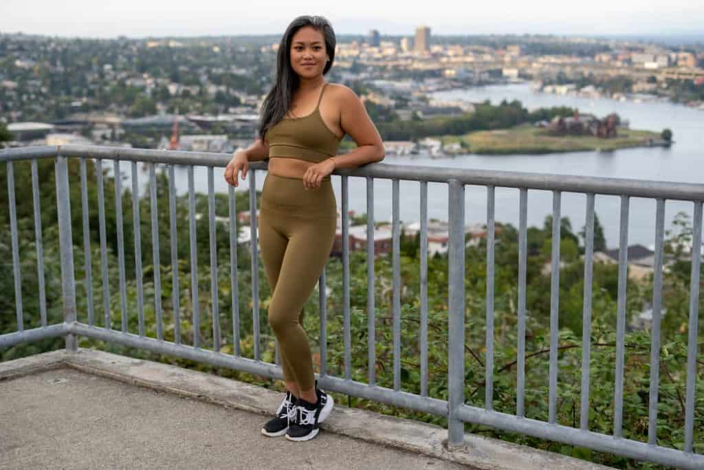Woman wearing brown postpartum leggings leaning against railing