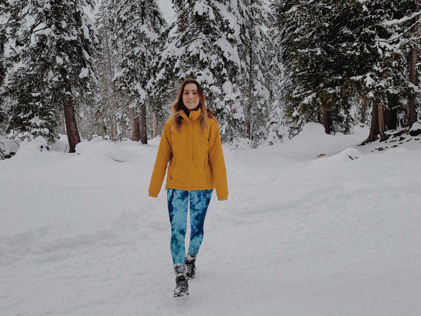 Woman walking in a snow covered ground wearing printed velvet leggings