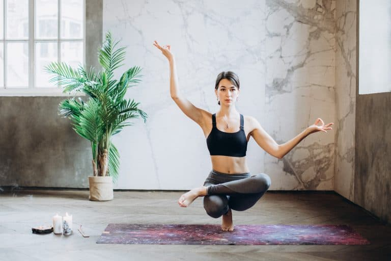 Woman practicing yoga wearing cellulite hiding yoga pants