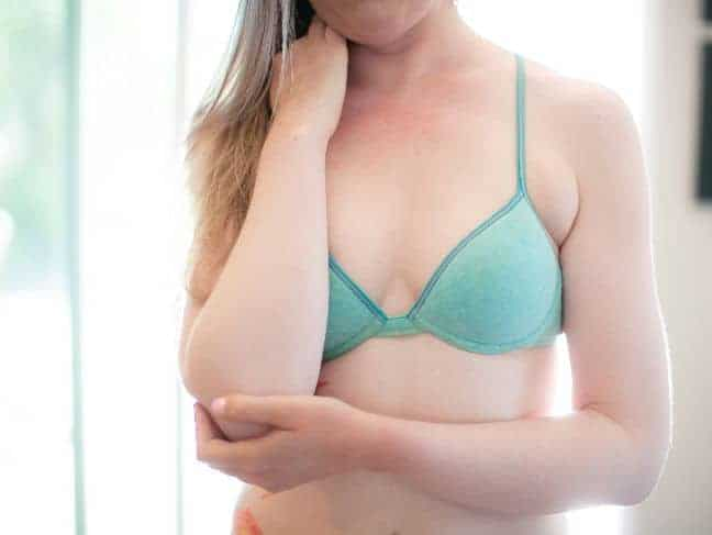 Woman wearing a light green bra holding her elbow