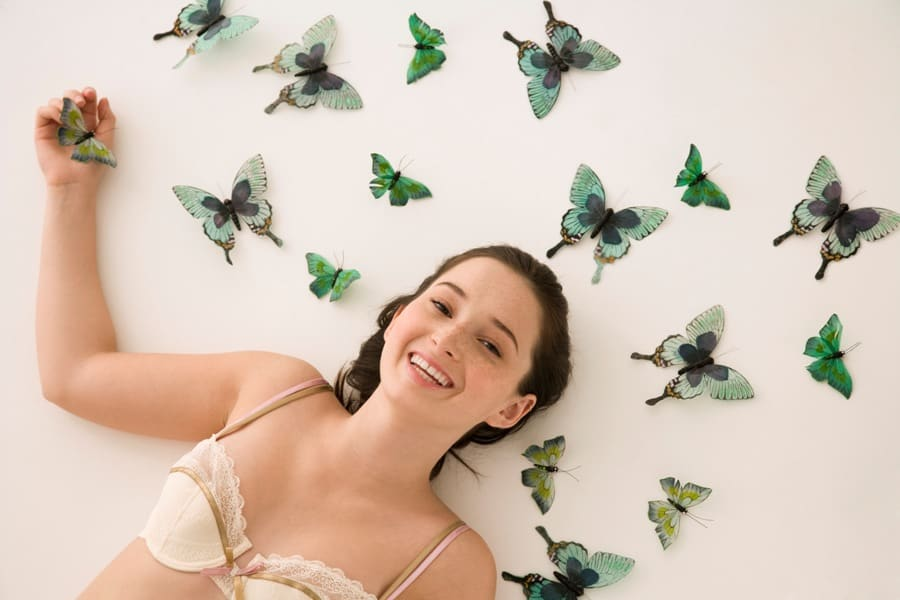 Woman lying down surrounded by butterflies