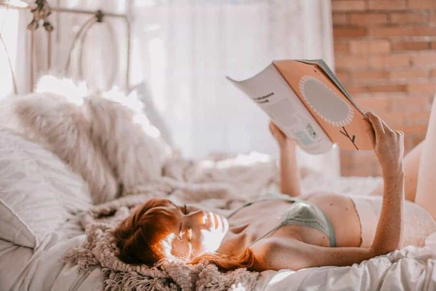 Woman lying on her bed and reading a magazine while wearing her cooling bra