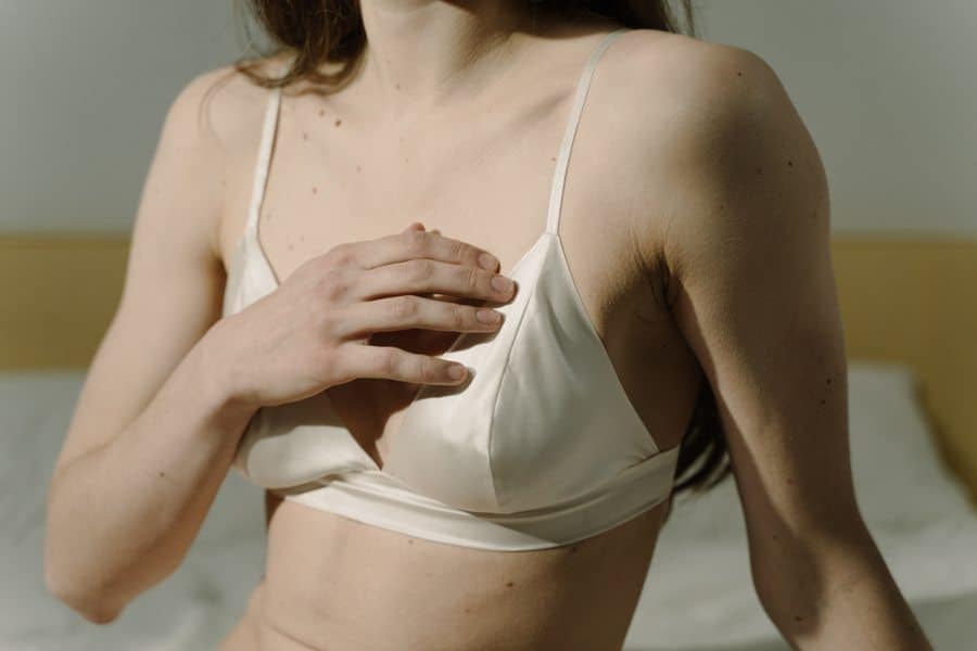 Woman with wide set breasts wearing a white bra