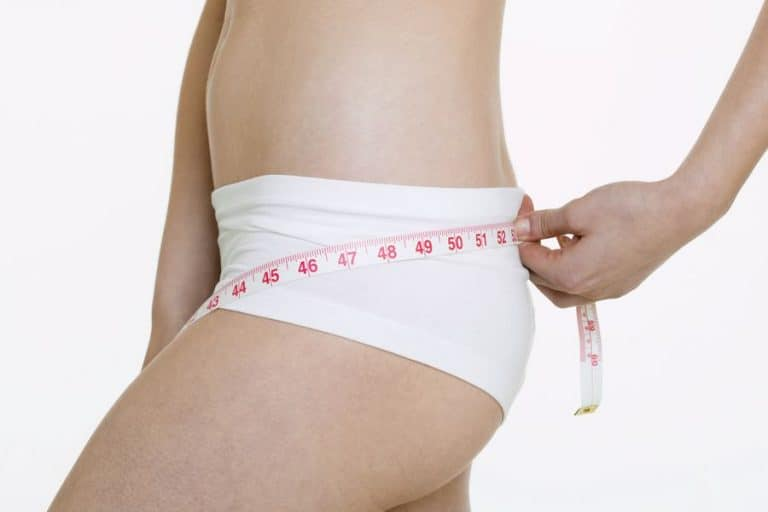 Woman measuring her hips while wearing rear lifting shapewear