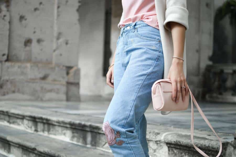 Woman wearing light blue jeans with rose print
