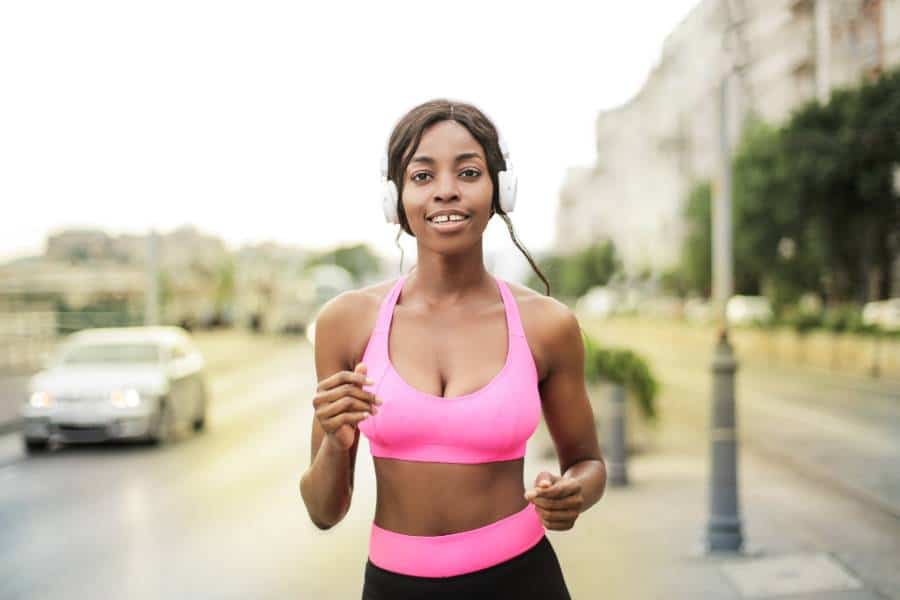 Woman wearing a pink push-up sports bra while jogging