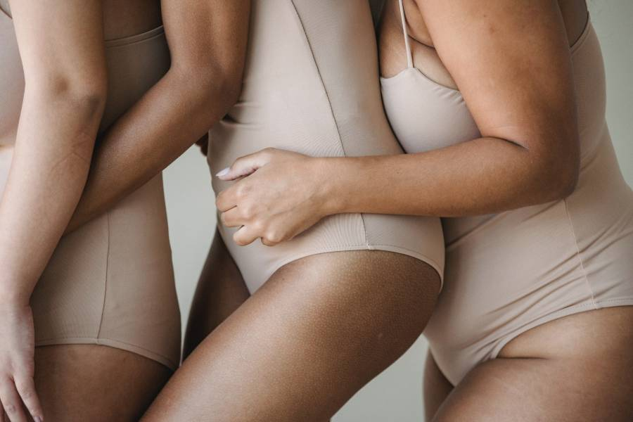 Three women wearing shapewear hugging each other from behind