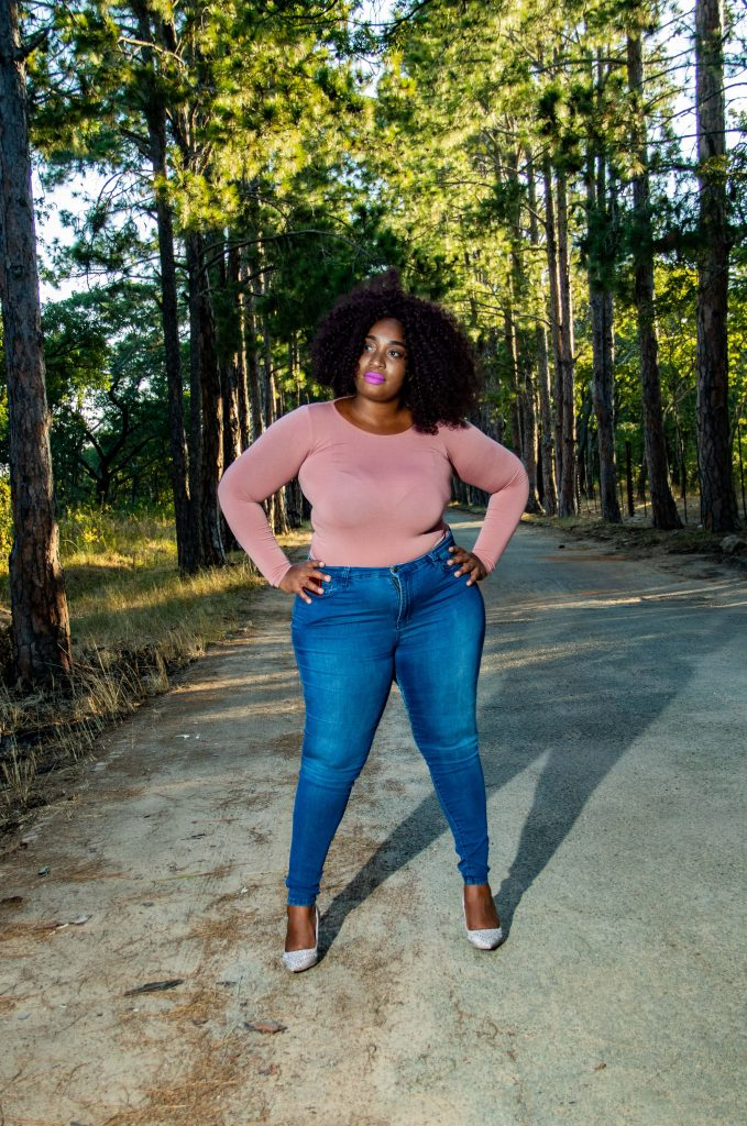 Woman wearing a pink long sleeved shirt with fitted jeans