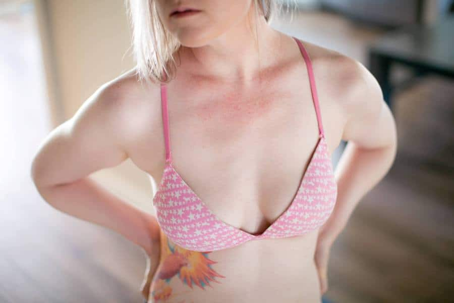 Woman with wide set breasts wearing a pink bra