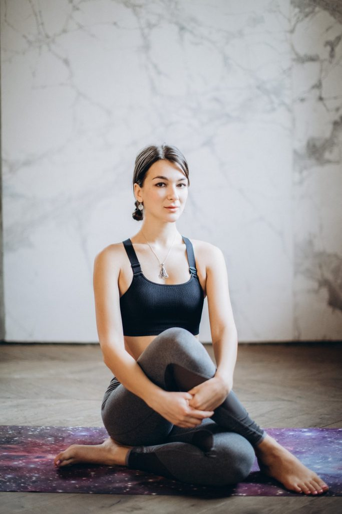 Woman resting after a yoga session while wearing a sports bra and leggings