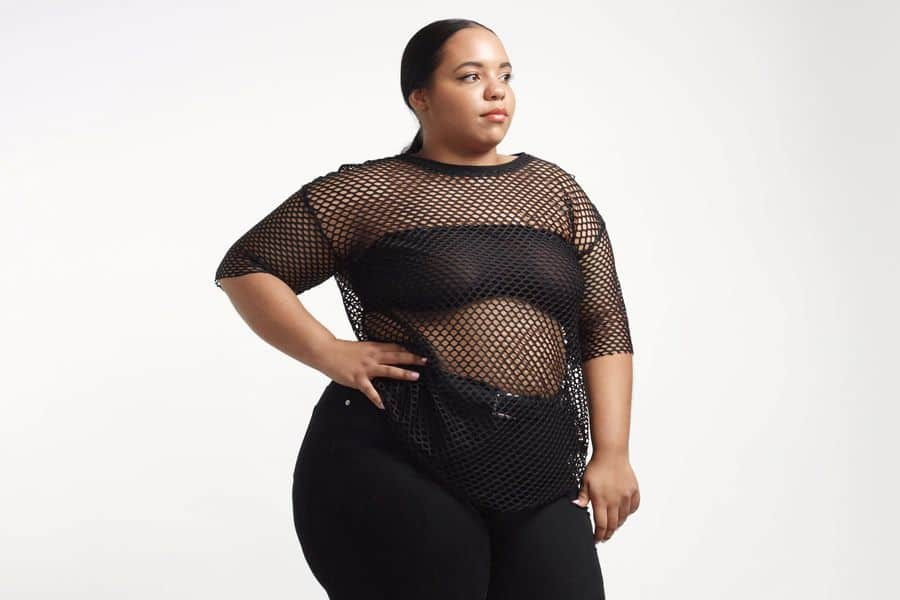 Plus size model wearing a sheer shirt with a black strapless bra underneath