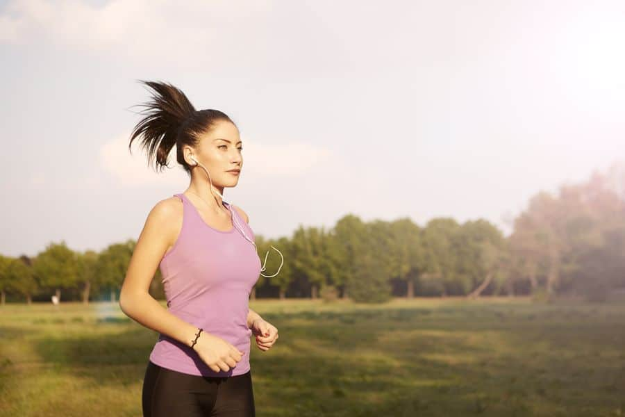 Woman listening to her earphones while running and wearing a pink tank top