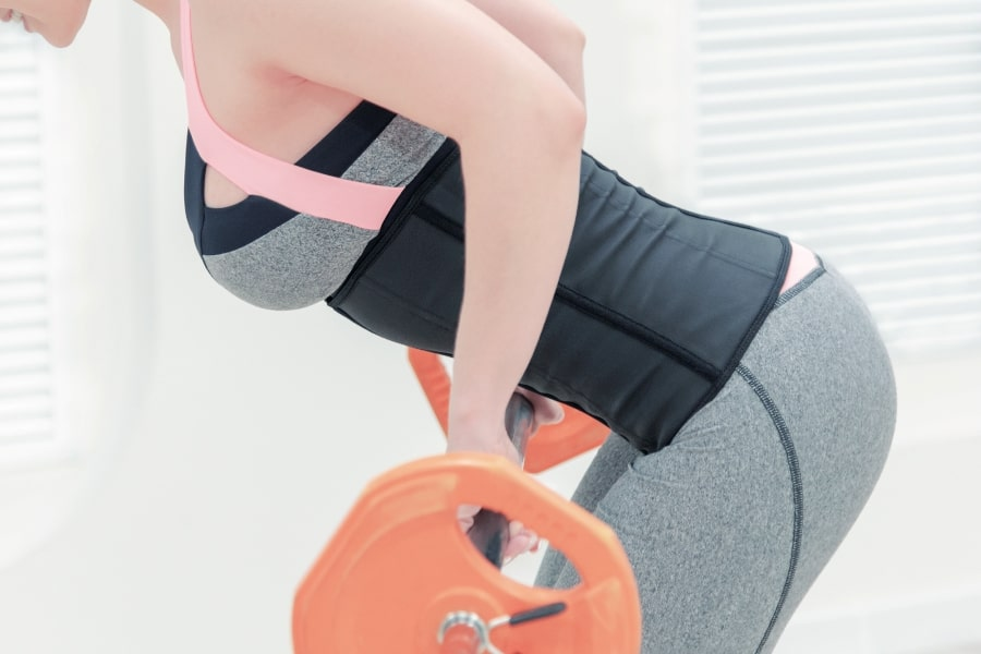 Girl wearing a waist trainer while lifting weights