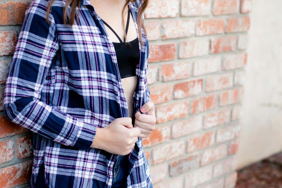 Woman wearing a plaid top over her black bralette